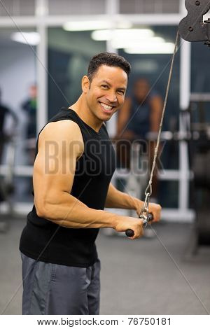 muscular man using triceps pull down in gym