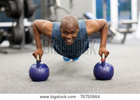 happy young african man doing push-ups exercise with kettle bells