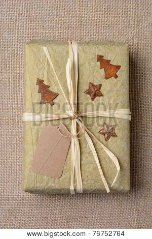High angle closeup of a gold tissue paper wrapped Christmas present on a burlap surface. The gift is tied with raffia and has antique star and tree tin ornaments. Vertical format.