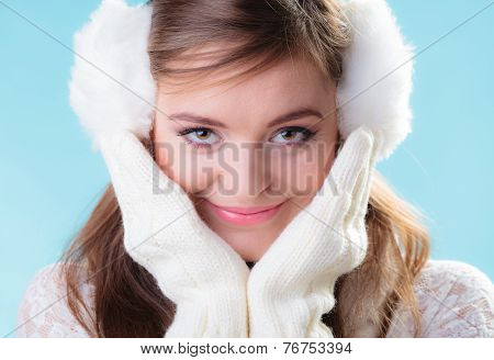 Happy Woman In White Earmuffs On Blue