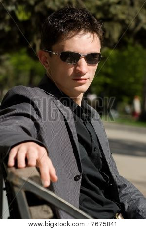 Man In Sunglasses And Jacket Sitting On A Bench In The Middle Of A Day