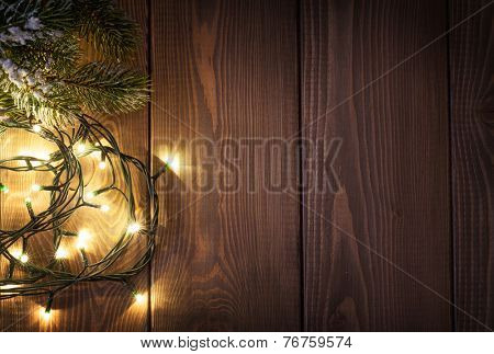 Christmas lights and snow fir tree over wooden background with copy space