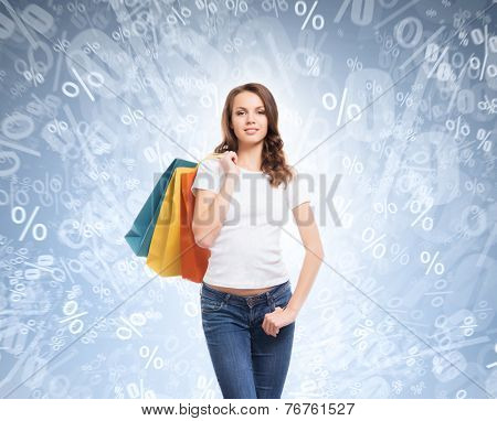 A young, attractive and happy teenage shopping girl with bright shopping bags. Christmas and winter seasonal discounts concept.