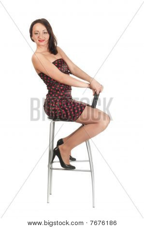 Beautiful White Woman In Dress On Armchair.