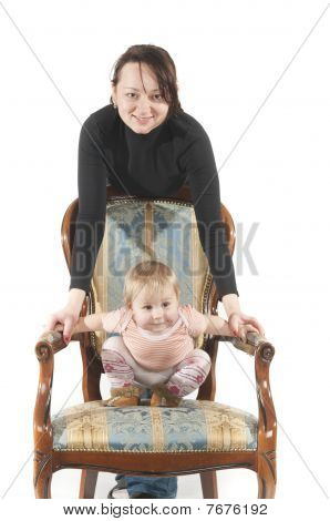 Young Mother Ans Daughter Are Sitting On Chair. Isolated Over White Background