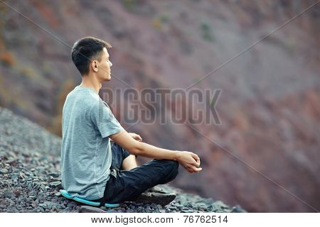 Young Man Relaxing On Rocky Cliff