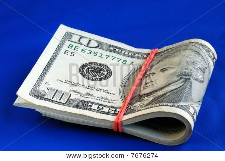 A strap of ten dollar bills isolated on blue