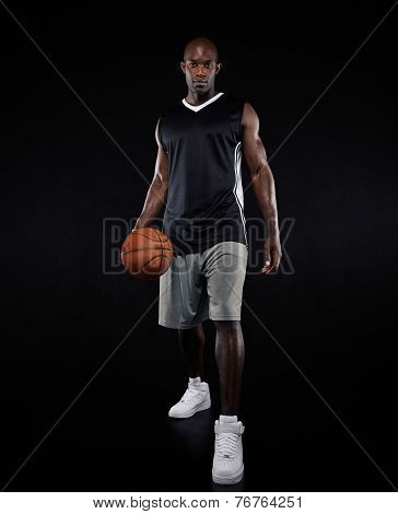 Confident Young Basketball Player Over Black Background