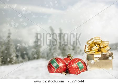 Golden gift box and red Christmas decorations in the snow, snow cowered pine trees in the background