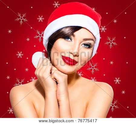 Christmas Woman. Beauty Model Girl in Santa Hat over holiday red Background with snowflakes. Holiday make up. Funny Smiling Surprised Woman Portrait. Red Lips and Manicure. Beautiful Holiday Makeup