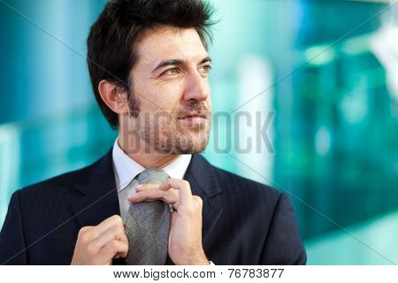 Handsome businessman adjusting his tie