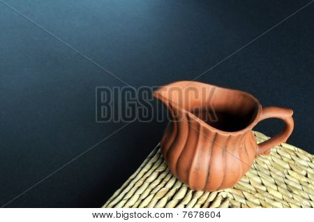 Old clay pot on grass mat