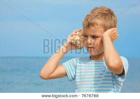 menino com ruído escuta de concha do mar.