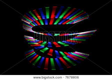 Cores luminosas da trilha do arco-íris em forma de espiral sobre fundo preto. Isolado.