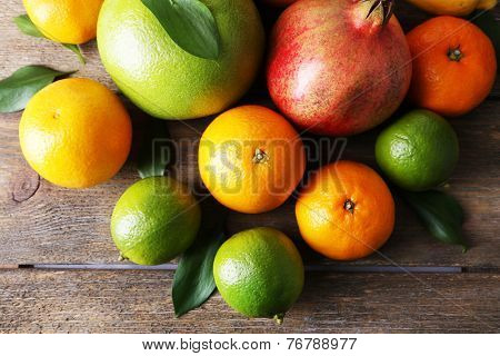 Ripe citrus with green leaves on wooden background