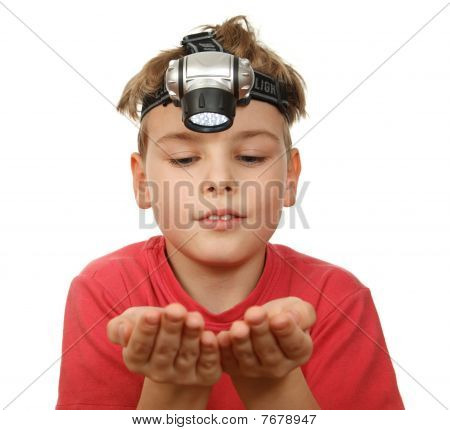 Portrait of boy with flashlight on his head on white