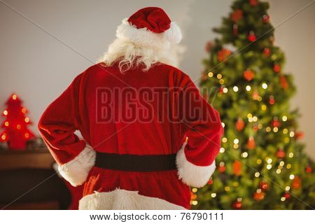 Rear view of santa standing in front of the christmas tree at home in the living room