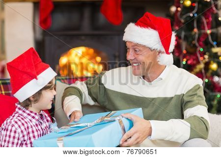 Son giving father a christmas gift on the couch at home in the living room