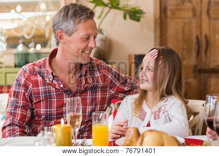 Smiling father and daughter during the dinner at home in the living room