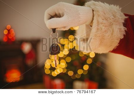 Hand of father christmas holding car key at home in the living room