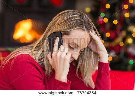 Upset young woman looking down while calling on phone at home in the living room