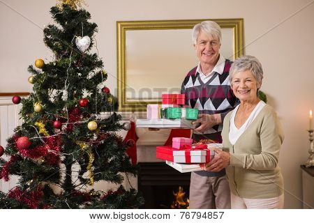 Senior couple swapping gifts by their christmas tree at home in the living room