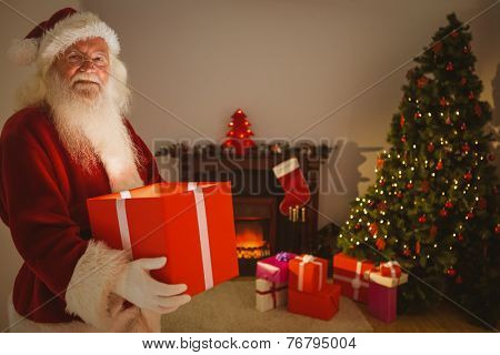 Happy santa delivering presents at christmas eve at home in the living room