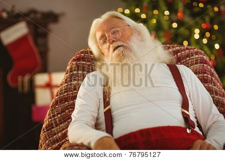 Santa claus sleeping on the armchair at home in the living room