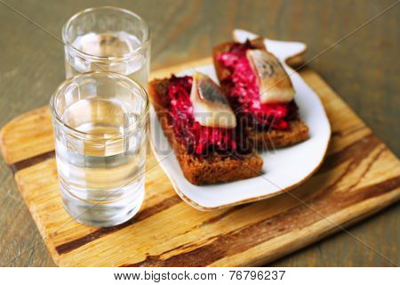 Canape herring with beets on rye toasts, on wooden board, and glass of vodka on wooden table background