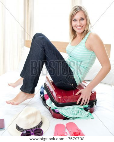 Attractive Woman Trying To Close Her Suitcase