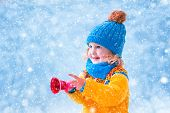 foto of blue-bell  - Adorable little girl cute toddler in a blue knitted hat and yellow nordic sweater playing with Christmas toy bell catching snow flakes having fun outdoors in a beautiful winter park - JPG