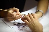 stock photo of nail paint  - Color shot of a person applying nail paint on nails - JPG