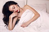 pic of sleeping beauty  - fashion interior photo of beautiful young woman with dark hair and bright makeup lying in bed at bedroom - JPG