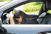 stock photo of deprivation  - Closeup portrait tired young attractive woman with short attention span driving her car after long hours trip trying to stay awake at wheel isolated outside background - JPG