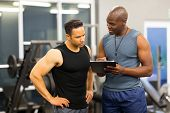 stock photo of health  - african personal trainer helping man to fill the membership form of health club - JPG