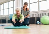 stock photo of personal assistant  - Elderly woman being helped by her instructor in the gym for exercising - JPG
