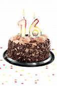 picture of sweet sixteen  - Chocolate birthday cake surrounded by confetti with lit candle for an sixteenth birthday or anniversary celebration - JPG