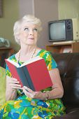 stock photo of tawdry  - Enchanted woman with grin reading a book - JPG
