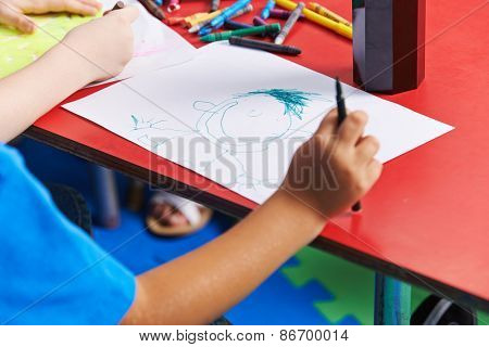 Child drawing person on paper with felt pen in kindergarten