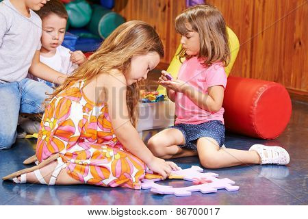 Children playing together in preschool with a big jigsaw puzzle