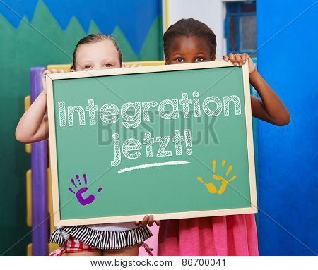 Two children demanding on chalkboard in German