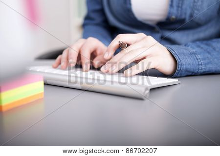 Businesswoman Typing In Data To Her Computer
