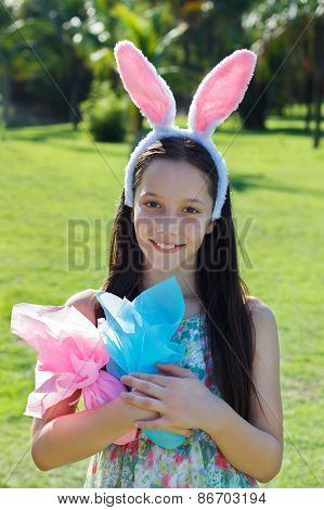 Smiling Happy Teen Girl With Rabbit Ears And Easter Chocolate Eggs