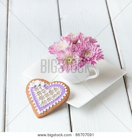 Cup Full Of Pink  Mum Flowers And  Heart Shape Cookie On White Wooden Table.