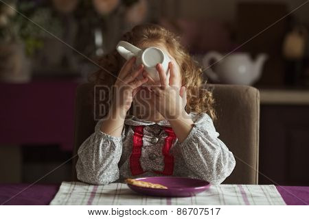 Little Girl Drinks Tea From A Large Cup