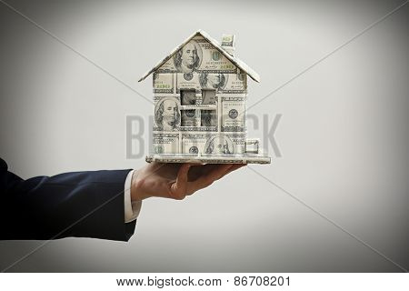 Model of house made of money in male hand on gray background