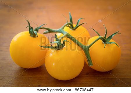 Tiny yellow tomatoes on a wood background.
