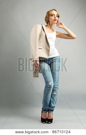 Beautiful young woman in jacket and jeans posing on light background