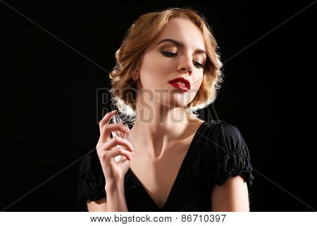 Beautiful young woman with perfume bottle on black background