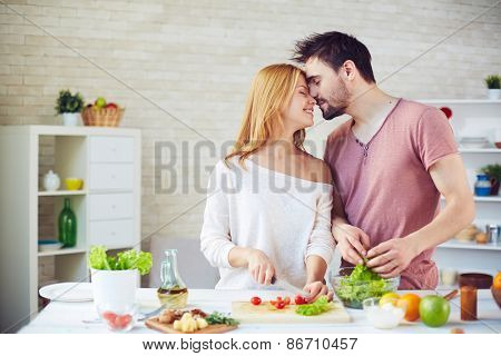Amorous young couple cooking in the kitchen